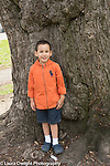 3 year old boy outside portrait standing near large tree, full length
