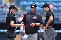 Charleston RiverDogs hitting coach Greg Colbrunn with first base umpire Jason Johnson and home plate umpire Sam before a game against the Asheville Tourists at McCormick Field on July 10, 2016 in Asheville, North Carolina. The Tourists defeated the RiverDogs 4-2. (Tony Farlow/Four Seam Images)