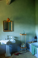 A gilt-framed mirror hangs above the sink in this eau-de-nil coloured bathroom