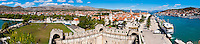 Panoramic photo of Trogir water front, Kamerlengo Fortress and Trogir football pitch, Obala Bana Berislavica, Trogir, Dalmatian Coast, Croatia, Europe. This panoramic photo of Obala Bana Berislavica, the main road along the water front in Trogir was taken from Kamerlengo Fortress (Gradina Kamerlengo). It shows Kamerlengo Fortress (Gradina Kamerlengo) in the foreground and the football pitch on the far left. From right to left, the three main Cathedral bell towers that are visible are; Church and Monastery of St Dominic, Cathedral of St Lawrence and St Michael Monastery Church Bellfry. Trogir is a beautiful old town on the Dalmatian Coast of Croatia and is on the UNESCO World Heritage List thanks to it's stunning Romanesque Cathedral's and architecture. Inside the walls of the old town Trogir, the cobbled streets are complemented by beautiful buildings and towering spires. After visiting the many sites, there is always the option of a walk along Obala Bana Berislavica, the main street along the waterfront in Trogir that runs alongside the bright blue Adriatic Sea of the Dalmation Coast of Croatia.