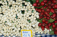 Spring onions and radishes on vegetable market stall.