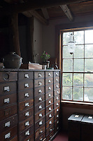 One wall of a guest bedroom is lined with a bank of antique office drawers