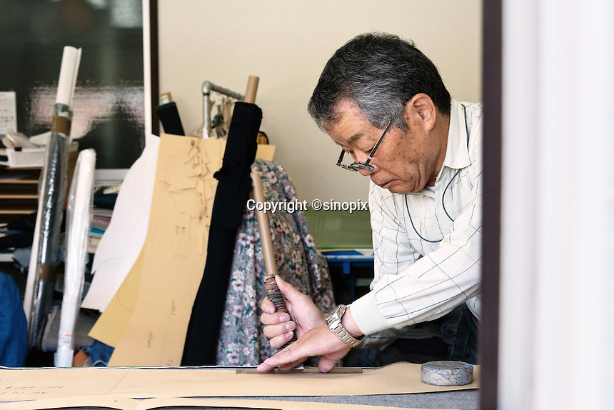MAY 15, 2014 - KOJIMA, KURASHIKI, JAPAN: Totaro Yamashita cuts Denim fabric for hand made ordered jeans at the Betty Smith's factory. (Photograph / Ko Sasaki)