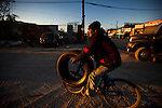 QUEENS, NY -- OCTOBER 25, 2013:  A man carries a car tire on a bicycle in Willets Point on October 25, 2013 in Queens, NY.  PHOTOGRAPH  BY MICHAEL NAGLE FOR THE NEW YORK TIMES