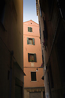 Building showing window shutters at the end of a narrow Venitian alleyway.Venice Italy