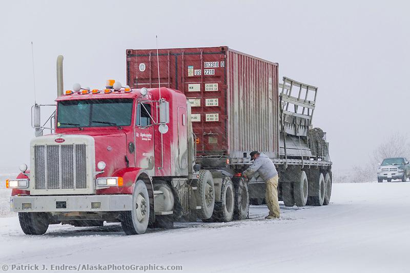 Semi tractor trailer, driver puts chains on truck before crossing Atigun pass, James Dalton Highway, Brooks Range, Arctic, Alaska