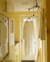Clothes hang from an old-fashioned pulley drying rack in this narrow utility room.