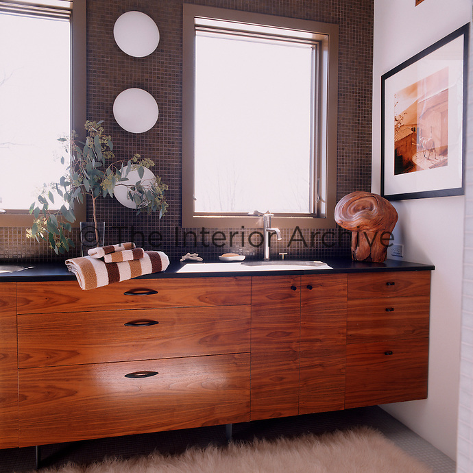 Ludick designed and built the walnut cabinetry in the master bathroom