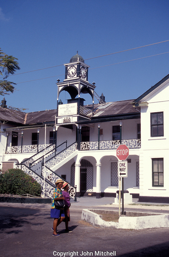 Two colourfully dressed black women walking past the Supreme Court of Belize building in downtown  Belize City, Belize