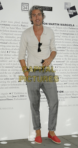 GEORGE LAMB.The Maison Martin  Margiela '20' Exhibition private view, Somerset House, London, England..June 2nd, 2010.full length grey gray trousers beige top rolled turned up red loafers shoes hand in pocket .CAP/CAN.©Can Nguyen/Capital Pictures.