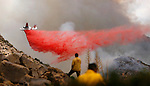 07-06-news-RIP-03.jpg.An brush fire bomber drops fire retardant on portion of the 300-acre Covington fire that occurred in the Joshua Tree National Park near Yucca Valley on Thursday, July 20, 2006. The firefighter on the left is Phil Veneris, from CDF. He is watching the effectiveness of the drop and will relay back to the command center the direction of travel of the brush fire.