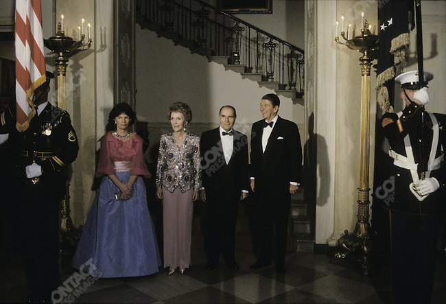 French President Francois Mitterrand standing  with US President Ronald Reagan and their wives, Danielle Mitterrand and Nancy Reagan, during a state diner at the White House, Washington, D.C., March 22nd 1984