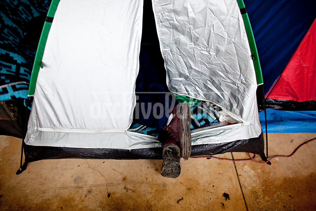 A picture dated  October 16, 2011 shows the feet of a man resting in his tent in the town of Chuspipata, 30 miles from the capital city of La Paz, having breakfast during a break of the two month long march in defence of the TIPNIS while the rest of the country votes for the Bolivian elections to elect all new members of the judicial system for the first time in the history of the country.   PATRICIO CROOKER