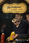 © Joel Goodman - 07973 332324 . 21 November 2013 . Manchester , UK . Customer at a sausage stall in Exchange Square . Candid photos of the Christmas Markets in Manchester City Centre . Photo credit : Joel Goodman