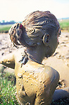 AT5BT7 Girl covered in mud after mud bathing in salt marsh mud at Butley Creek Suffolk England