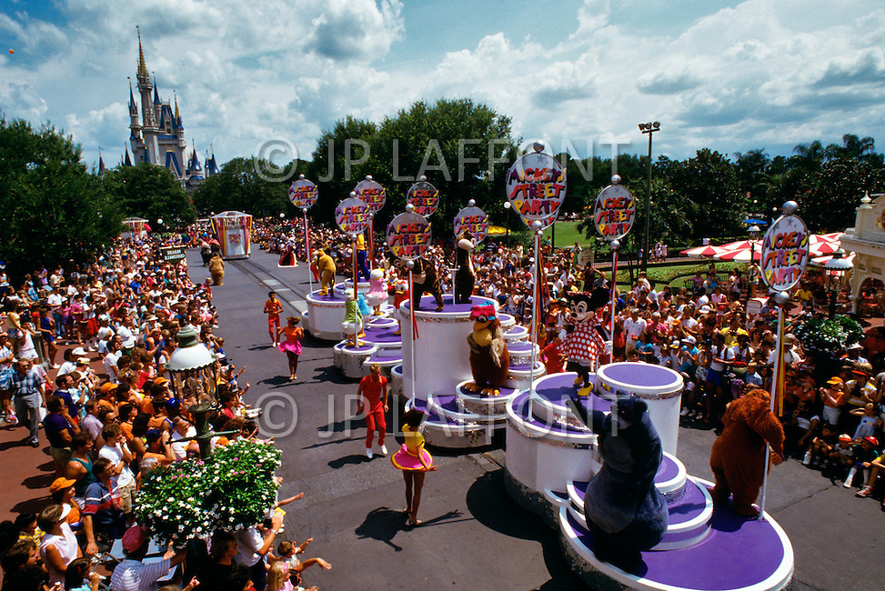 Orlando, Florida - Circa 1986. Crowds watch Disney World performers at Mickey's Street Party (held between January 1985 - 1986). Characters featured in the parade include Pluto, Donald Duck, Chip 'n' Dale, the rooster Chanticleer, Minnie Mouse and Baloo the Bear. Disney World is a world-renowned entertainment complex that opened October 1, 1971 in Lake Buena Vista, FL. Now known as the Walt Disney World Resort, the property covers 25,000 acres and has an annual attendance of 52.5million people.