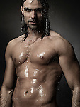 Dramatic portrait of a young man with wet bare torso standing under a shower with water running down his body