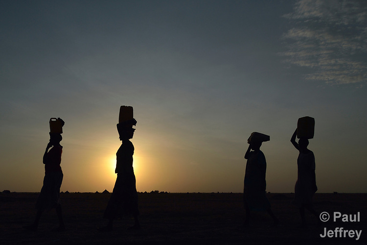 Women carry water to their homes at sunrise on April 12, 2017, in Dong Boma, a Dinka village in South Sudan's Jonglei State. Most of the villagers recently returned home after being displaced by rebel soldiers in December, 2013. <br /> <br /> The women obtained water from a well drilled by the Lutheran World Federation, a member of the ACT Alliance, which is helping villagers restart their lives with support for housing, livelihood, and food security.