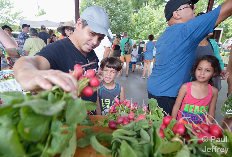 Serguei Torres Miranda, a refugee from Cuba, shows radishes to his children Andy and Ariadna in the Durham Farmers' Market in Durham, North Carolina. The family was resettled in Durham by Church World Service, which resettles refugees in North Carolina and throughout the United States.<br /> <br /> Photo by Paul Jeffrey for Church World Service.