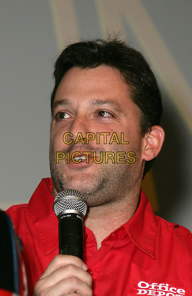 TONY STEWART.Lagasse's Stadium Welcomes NASCAR Champion Tony Stewart at the Palazzo Resort Hotel and Casino, Las Vegas, Nevada, USA, 27th February 2010..portrait headshot stubble facial hair mouth open  red shirt microphone speaking .CAP/ADM/MJT.©MJT/Admedia/Capital Pictures
