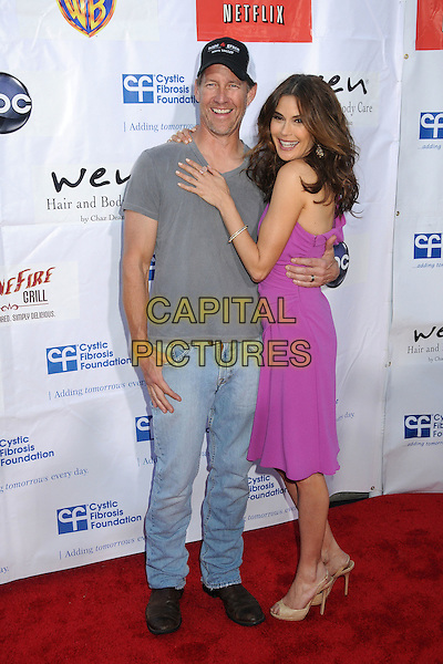 "James Denton, Teri Hatcher.""Desperate Housewives"" Wisteria Lane Block Party held at Universal Studios Backlot,  Universal City, California, USA, 21st April 2012..full length  grey gray t-shirt cap hat pink purple one shoulder dress arm around smiling jeans  .CAP/ADM/BP.©Byron Purvis/AdMedia/Capital Pictures."