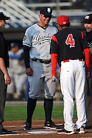 Staten Island Yankees manager Mario Garza (28) during the lineup exchange with Angel Espada (4) before a game against the Batavia Muckdogs on August 6, 2014 at Dwyer Stadium in Batavia, New York.  Batavia defeated Staten Island 5-3.  (Mike Janes/Four Seam Images)
