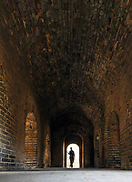 Woman standing in arched door way opening inside a Great Wall watch tower, Simatai Great Wall, China, Asia