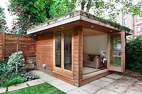 A wooden cabin style summer house with a living roof in the garden of a town house.