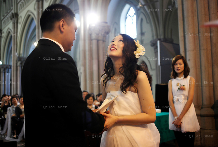 Coca Dai and Juan Juan take their wedding vows during their wedding ceremony at the Xujiahui Catholic Church in Shanghai, China on 23 May 2009. A hip street artist and a recent Catholic convert, Mr. Dai is one of many young Chinese embracing religion, perhaps to fill the lack of belief and ideology in an authoritarian communist China that embraces the most extreme form of capitalism in practice. The Chinese government and the Vatican have a long history of simmering mutual distrust and suspicion, as two parties compete for the control of the Chinese Catholic church, with some 15 million and growing number of faithfuls.  Overall Christians now number over 110 million in China, which makes it the third largest Christian nation in the world.