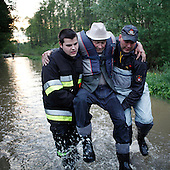 BORKI, POLAND, MAY 24, 2010:.Rescue workers evacuating villager Mr.Waszkiewicz..The latest chapter of disastrous floods in Poland has been opened yesterday, May 23, 2010, after Vistula river broke its banks and flooded over 25 villages causing evacualtion of most inhabitants..Photo by Piotr Malecki / Napo Images..BORKI, POLSKA, 24/05/2010:.Strazacy niosa mieszkanca wsi Pana Waszkiewicza. Najnowszy akt straszliwych tegorocznych powodzi zostal rozpoczety wczoraj gdy Wisla przerwala waly na wysokosci wsi Swiniary kolo Plocka..Fot: Piotr Malecki / Napo Images ..