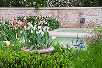 Waterfall feature, container of white tulips, evergreen shrubs, irises, Zantedeschia calla lilies, in pastel shades with stone wall in pretty garden in spring flowers