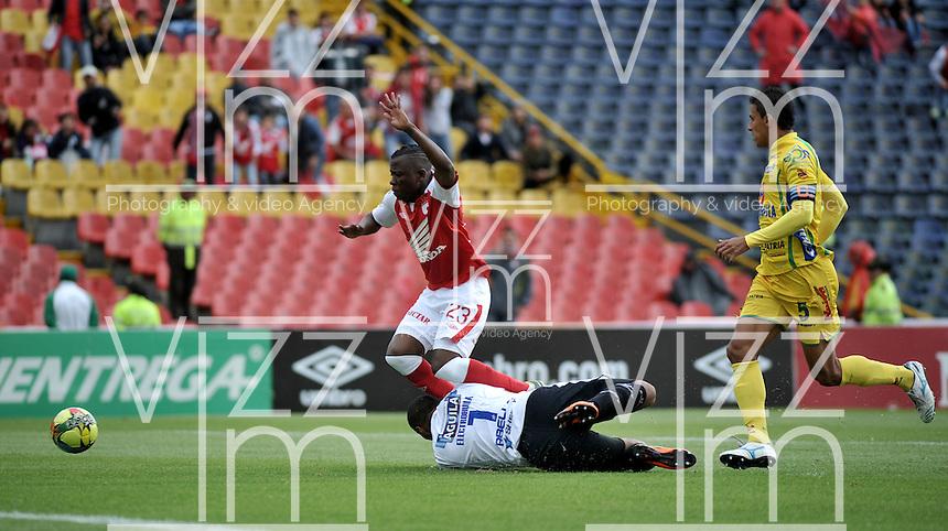 BOGOTA - COLOMBIA -10 -11-2013: Carlos Abella (Cent.), portero de Atletico Huila, comete falta a Jefferson Cuero (Izq.) durante del partido por la fecha 18 de la Liga Postobon II-2013, jugado en el estadio Nemesio Camacho El Campin de la ciudad de Bogota.  / Carlos Abella (R), goalkeeper of Atletico Huila fouls to Jefferson Cuero (L), during a match for the 18 date of the Postobon Leaguje II-2013 at the Nemesio Camacho El Campin Stadium in Bogota city, Photo: VizzorImage  / Luis Ramirez / Staff.