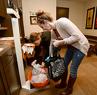 NWA Democrat-Gazette/ANDY SHUPE<br /> Karri Myers (left), greeting specialist for Jeff Ward Pediatric Dentistry in Fayetteville, and Summer Cronin of Rogers weigh 21 pounds of Halloween candy collected by Cronin's sons Cash, 10; Preston, 7; and Ace, 4; during the dentist office's fourth annual Halloween Candy Buyback at the office in Fayetteville. The office paid a dollar per pound for the candy and plans to donate it to military service members along with letters written by the children who returned the candy through Operation Gratitude. Last year, 740 pounds of candy was collected and donated.