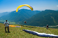 Kobarid, Julian Alps, Slovenia, July 2011. Catching the thermals while being a tandem paragling passenger. Slovenia boast a very spectacular carstic landscape with high limestone rock formations oozing with waterfalls, and fast flowing cristal clear waters that run through the Soca from the Triglav National Park to the Adriatic Sea. The Julian Alps are a paradise for outdoor adventure and adrenaline sports. The 3 centers for all activities are Bovec, Kobarid and Tolmin.  Photo by Frits Meyst/Adventure4ever.com