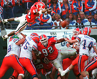 Georgia freshman cornerback  Champ Bailey does his best Superman imitation as he flies over the Florida Gator offensive line and reaches out his hand to block an extra-point attempt by Gator's kicker #14 Bart Edmiston.