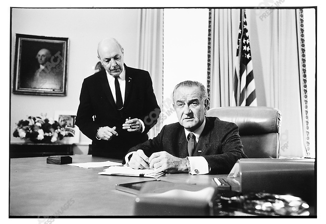 President Lyndon Johnson with reporters as he signs the 1969 Budget law. (unidentified aid at left). The White House, Washington D.C. USA. October, 1968.