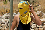 A Palestinian youth uses a T-shirt to hide his face in anticipation of a clash following the suppression of a non-violent demonstration against Israel's controversial separation barrier by Israeli soldiers in the West Bank town of Beit Jala, near Bethlehem on 11/07/2010. Ultimately no clash occurred at this location, instead a brief skirmish ensued on the opposite side of the valley.