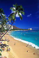 People swimming in the blue waters of Waikiki beach with leaning palm trees and Diamond head in backround