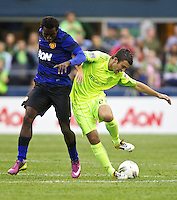 Seattle Sounders FC forward Servando Carrasco, right, battles Manchester United defender Mame Biram Diouf during play at CenturyLink Field in Seattle Wednesday July 20, 2011. Manchester United won the match 7-0.