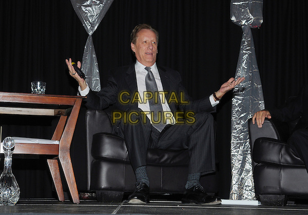 Actor James Woods attends 'A Conversation With James Woods' presented by CARSTAR Automotive Canada Inc. in support of Cystic Fibrosis Canada at Carmen's Banquet and Convention Centre, Hamilton, Ontario, Canada..November 20th, 2011.full length black suit grey gray tie white shirt hands arms sitting .CAP/ADM/BPC.©Brent Perniac/AdMedia/Capital Pictures.