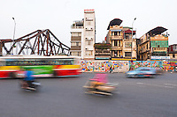 Traffic buzzes past the colorful 3.85 km long Hanoi Ceramic Mosaic Mural. It is the world's largest ceramic mosaic built from ceramic tesserae.<br /> <br /> The Hanoi Ceramic wall was built in-line with the 1000th anniversary of the foundation of the capital Thăng Long in October 2010. The whole idea of transforming a boring dyke-wall into a colorful ceramic mosaic originated because of Nguyen Thu Thuy. She is a journalist and her idea won the Hanoi Architecture Contest. The preparations to decorate the walls started in 2007. People and artists from not only Vietnam but all over the world contributed in the making of this mural. With Terracotta structures of boats, dragons, lac birds, fish, pelicans surrounded by mosaic tiles, the decorative patterns are a visual narration of the country's history from different periods.