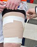 LAREN - Het dijbeen van Tomas Boerma wordt ingepakt met verband, zondag tijdens de hoofdklasse competitiewedstrijd mannen tussen Laren en Bloemendaal (1-4).  COPYRIGHT KOEN SUYK