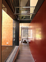 A corridor of shallow steps runs between a red lacquer wall and a plate glass window