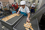 A member of staff at Oizen Shoten loads freshly baked sasa-kamabokoonto a tray at the company's factory in Tome City, Miyagi Prefecture, Japan on 11 Sept. 2012.  Photographer: Robert Gilhooly