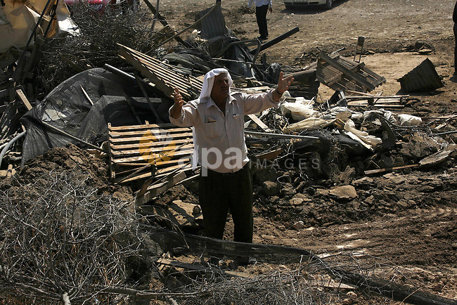 A Palestinian man reacts on the remains of his tent destroyed by the Israeli army, in the West Bank village of Faresiya near Tubas, Monday, July 19, 2010. Israeli forces demolished a cluster of tents and shacks belonging to Palestinians in the northern West Bank . Photo by Wagdi Eshtayah