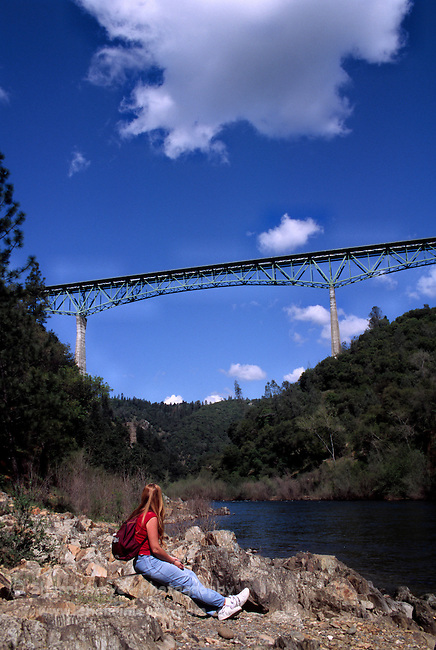 Woman viewing Foresthill Bridge from the confluence of the north and middle forks of the American River