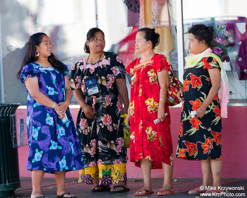 Micronesian women in colorful floral dresses standing on sidewalk in Chinatown, Downtown, Honolulu, Oahu, Hawaii