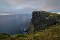 Hiker overlook the sea from summit of Fuglhuken mountain peak, Moskenesøy, Lofoten Islands, Norway