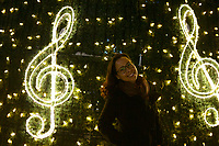 Lisbon, Portugal - December 23: A woman poses for a portrait with a christmas tree decorated with a treble clef in downtown Lisbon, Portugal December 23, 2019. <br /> The Christmas lights in Lisbon are getting more sophisticated and stunning each time, they are an attraction to locals and tourists to choose Lisbon as a place to spend the holidays<br /> (Photo by Luis Boza/VIEWpress/Corbis via Getty Images)