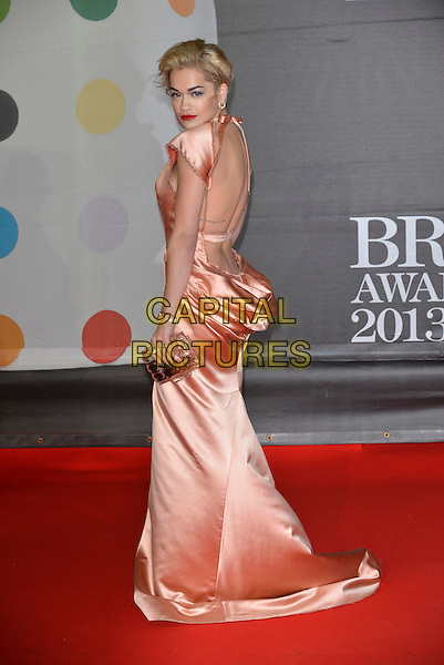 Rita Ora.The Brit Awards 2013 arrivals at the O2, Greenwich, London, England 20th February 2013.The Brits  full length peach dress silk satin halterneck ruched long maxi gold clutch bag train back over shoulder rear behind backless low cut out tattoo strap.CAP/PL.©Phil Loftus/Capital Pictures.